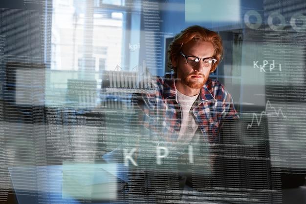 Plan d'un programmeur informatique aux cheveux roux qui travaille sur un nouveau code. il a l'air concentré et réfléchi. développeur en intelligence artificielle
