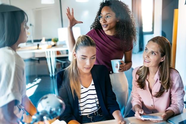 Plan de quatre femmes d'affaires intelligentes discutant et passant en revue les derniers travaux effectués sur l'ordinateur dans un espace de travail commun.
