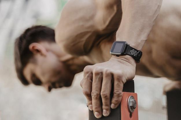 Plan rapproché d'athlète pratiquant la gymnastique suédoise avec smartwatch sur son poignet