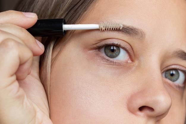Plan rapproché du visage d'une jeune femme caucasienne appliquant un gel de soin de sourcil avec une brosse