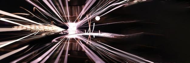Plan rapproché des étincelles lumineuses de la découpe laser du métal