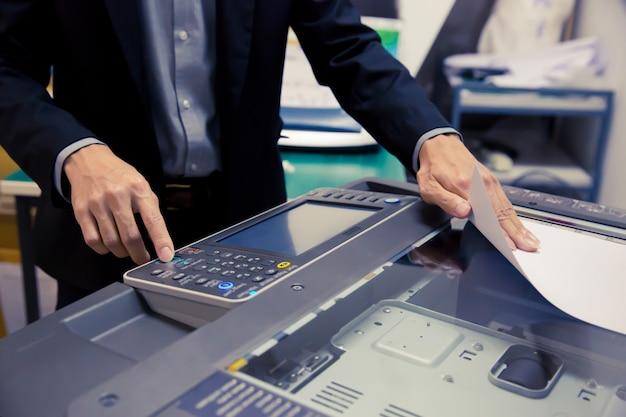 Plan rapproché les hommes d'affaires utilisent des photocopieurs.