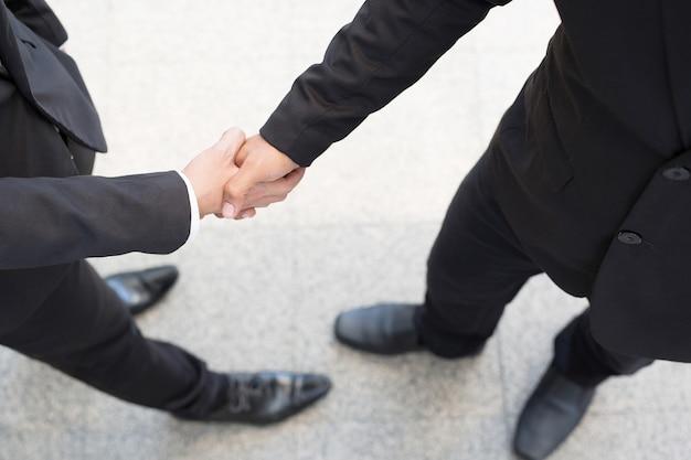 Plan rapproché d'un investisseur de poignée de main d'homme d'affaires entre deux collègues