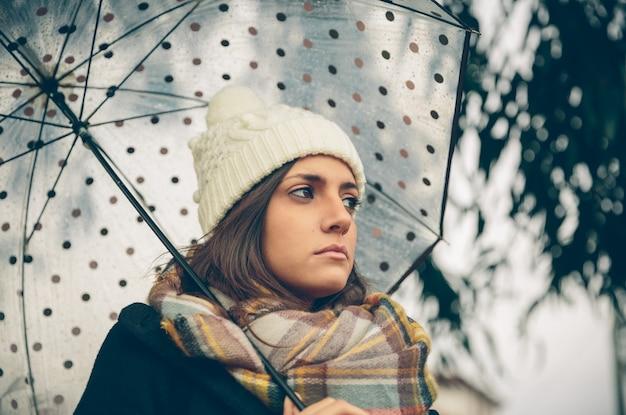 Plan rapproché de jeune belle fille sous un parapluie dans un jour pluvieux d'automne