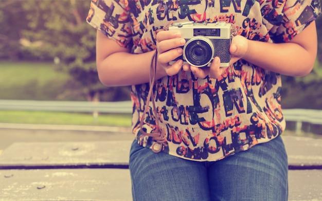Plan rapproché de la main de la femme tenant une caméra rétro. jeune photographe de jeune fille hipster avec caméra de film - style vintage filtre effet de couleur