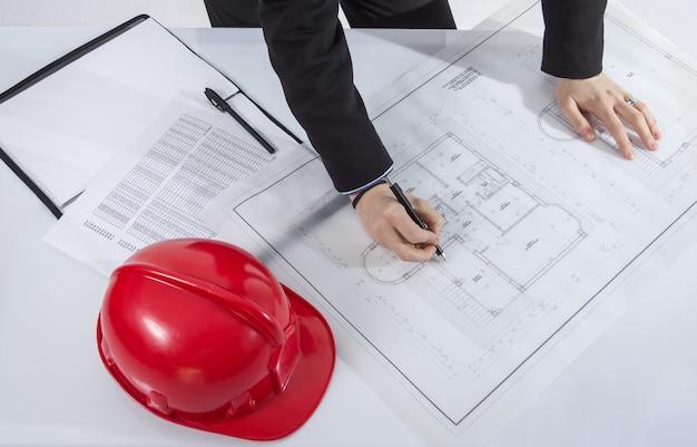 Plan rapproché des mains d'architectes révisant des plans de projet de maison