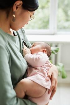 Plan rapproché de maman allaitant son bébé avant de dormir