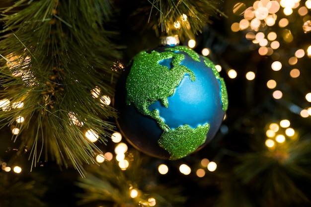 Plan rapproché de la planète terre d'ornement de décoration de boule de noël sur le fond du noël