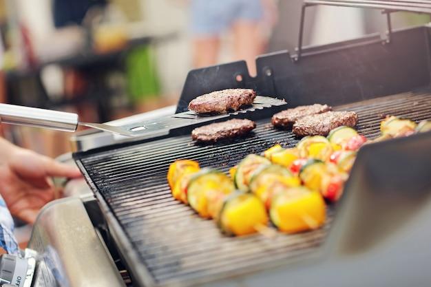 Plan rapproché des shashliks et des hamburgers grillés sur la grille