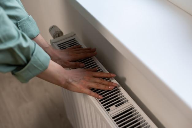 Plan rapproché d'un thermostat de radiateur avec la main de femme