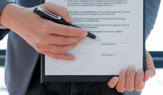 Plan recadré de l'entrepreneur a pointé le stylo sur le constructeur pour signer le contrat de construction de la maison.