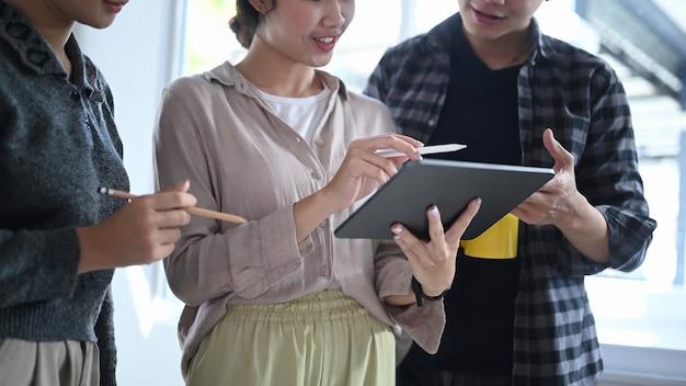 Plan recadré d'une équipe de concepteurs créatifs utilisant une tablette numérique et discutant d'un projet au bureau.