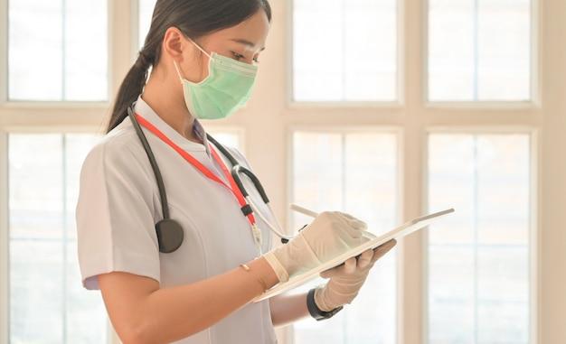 Plan recadré d'une infirmière portant des gants à l'aide d'une tablette pour enregistrer une personne infectée par le virus covid-19.