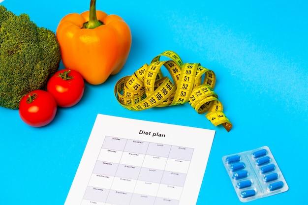 Plan de régime, pour les pilules de perte de poids et les légumes frais sur bleu.