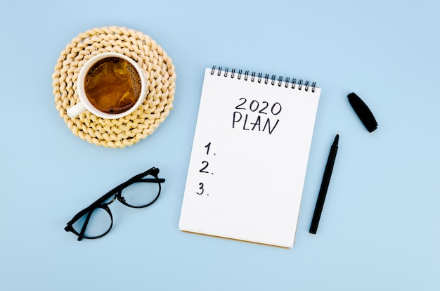 Plan de résolutions 2020 à vue de dessus avec café et verres