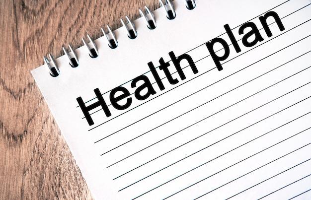 Plan de santé - texte sur un cahier blanc, fond en bois