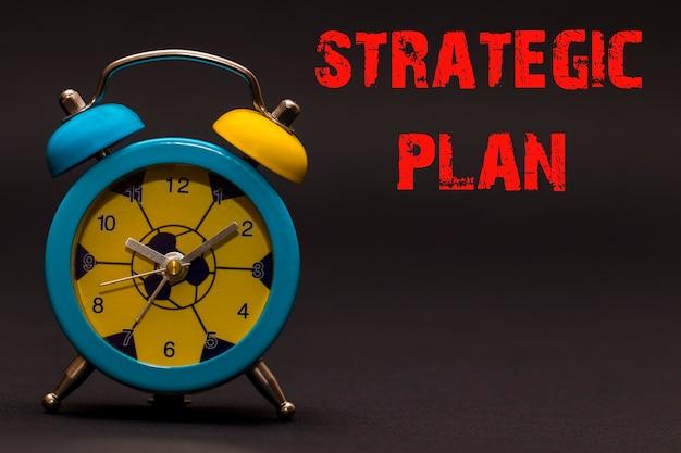 Plan stratégique écrit avec réveil sur fond de papier noir.