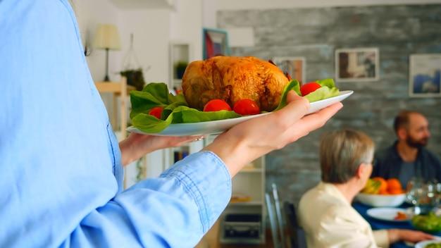 Plan suivi d'une jeune femme avec du poulet rôti lors d'un dîner en famille.