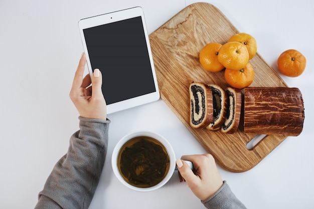 Plan supérieur de mains féminines tenant une tablette numérique pendant le petit déjeuner. une femme intelligente augmente son énergie avec une tasse de thé et mange des mandarines avec un gâteau roulé, se sentant bien le matin d'hiver.