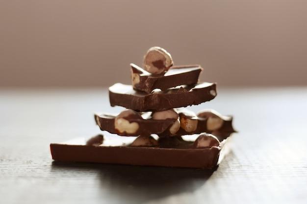 Plan d'une table brune avec du chocolat, une pyramide faite à la main à partir de morceaux de chocholate isolés sur une surface sombre, du lait chocholate aux noix