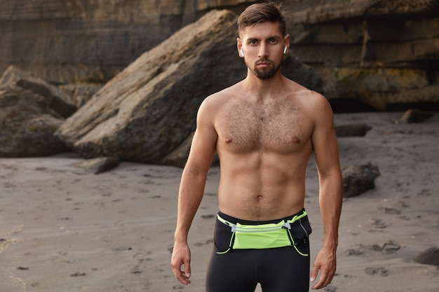 Plan à la taille du bodybuilder étant en bonne forme physique, regarde directement