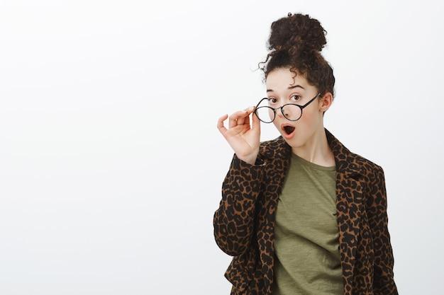 Plan à la taille d'une femme séduisante aux cheveux bouclés, surprise, en manteau léopard, enlevant ses lunettes et laissant tomber la mâchoire d'une rumeur incroyable impressionnante