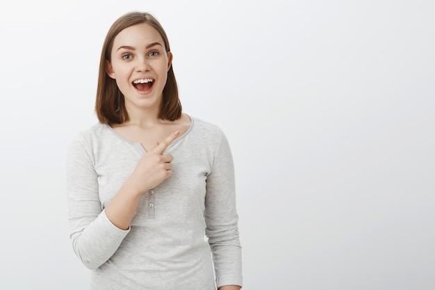 Plan de taille de jeune femme européenne agréable et enthousiaste avec de courts cheveux bruns souriant largement racontant une histoire intéressante sur l'espace de copie pointant vers le coin supérieur droit sur mur gris