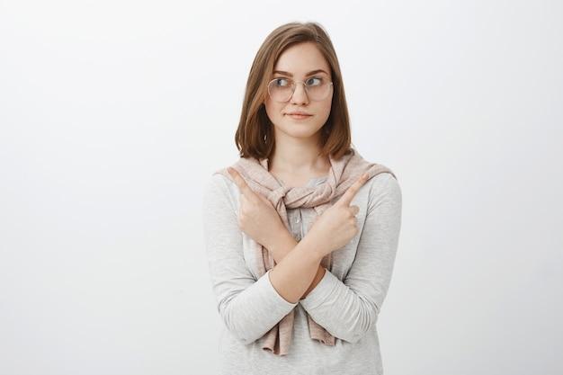 Plan de taille d'une jolie fille féminine détendue dans des verres avec des cheveux bruns courts croisant les bras sur le corps pointant de différents côtés gauche et droite faisant un choix ou une décision sur un mur gris