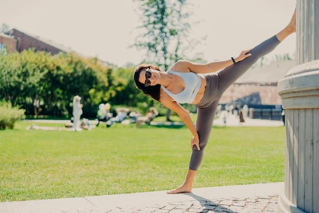 Plan sur toute la longueur de la femme brune étire les jambes montre une bonne flexibilité ne se divise habillé en lunettes de soleil de vêtements de sport pose à l'extérieur mène un mode de vie actif. concept de sport et d'aérobic de personnes.