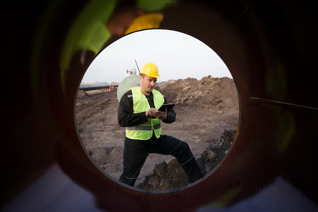 Plan d'un travailleur d'un champ pétrolifère vérifiant la qualité des conduites de gaz sur un chantier de construction