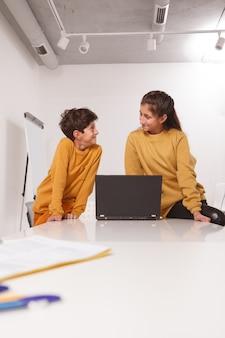 Plan vertical de l'adolescente et son petit frère souriant l'un à l'autre