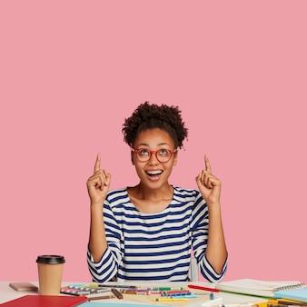 Plan vertical d'une belle femme artiste à la peau sombre et heureuse, pointe avec les deux index, porte un pull rayé, des modèles contre un mur rose, se sent excité, pose au bureau avec un cahier à spirale