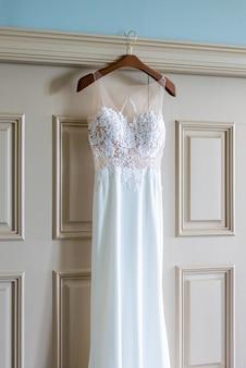 Plan vertical d'une belle robe de mariée blanche accrochée à la porte dans la chambre de la mariée