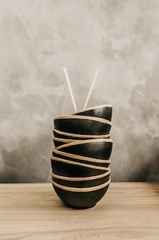 Plan vertical de bols de nourriture noirs empilés les uns sur les autres avec des baguettes sur le dessus