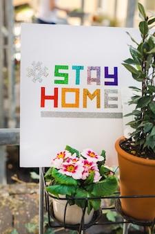 Plan vertical de carton blanc avec un texte coloré de «rester à la maison»