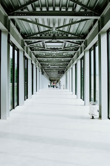 Plan vertical d'un couloir blanc avec des portes en verre et un plafond métallique dans un bâtiment moderne