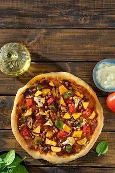 Plan vertical de délicieuses pizzas végétaliennes avec pesto de tomates, légumes et pignons de pin
