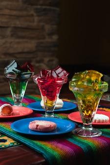 Plan vertical de desserts colorés à la gelée sucrée à côté d'assiettes à biscuits