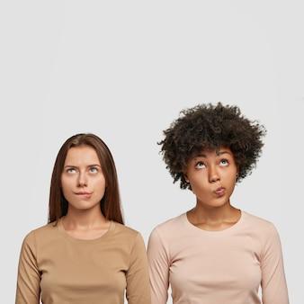 Plan vertical de deux femmes multiethniques confuses mordent les lèvres inférieures, regarde avec perplexité vers le haut, habillées avec désinvolture, tentent de résoudre le problème, isolé sur un mur blanc avec un espace vide au-dessus de la tête