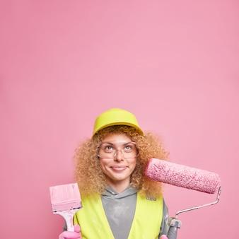 Plan vertical d'une employée de maintenance remettant la maison en bon état fournit un service professionnel pour la construction d'une maison ou d'un immeuble de bureaux utilise une brosse à rouleau pour la décoration intérieure