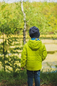 Plan vertical d'un enfant avec un manteau jaune jouant dans l'aire de jeux