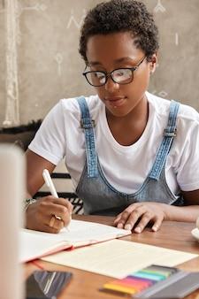 Plan vertical d'un étudiant à la peau sombre porte des lunettes transparentes, perçant, écrit des informations dans le journal