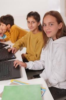 Plan vertical d'étudiants adolescentes souriant à la caméra tout en travaillant sur des ordinateurs à l'école