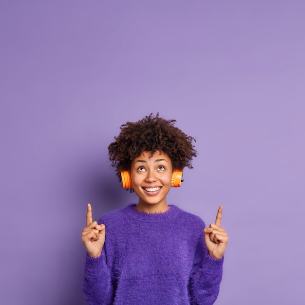 Plan vertical d'une femme afro-américaine heureuse en cavalier occasionnel indique ci-dessus sur l'espace de copie a des sourires d'expression positive du visage porte volontiers un casque stéréo sur les oreilles