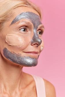 Plan vertical d'une femme d'âge moyen réfléchie regarde pensivement à distance applique un masque nettoyant