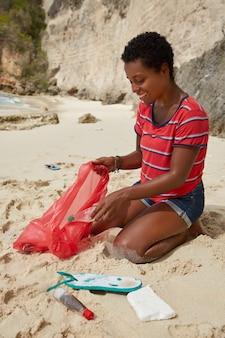 Plan vertical de la femme bénévole active heureuse ramasser la litière