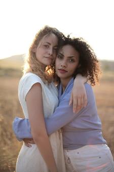 Plan vertical d'une femme blonde à côté d'un aux cheveux bouclés se serrant dans ses bras