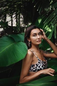 Plan vertical d'une femme brune avec bronzage doré, portant un bikini et des boucles d'oreilles, debout dans des feuilles de palmier tropical, regardant la caméra.