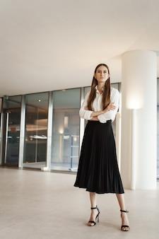 Plan vertical d'une femme confiante en jupe longue noire et chemisier blanc, les mains croisées sur sa poitrine dans une pose sûre d'elle-même.