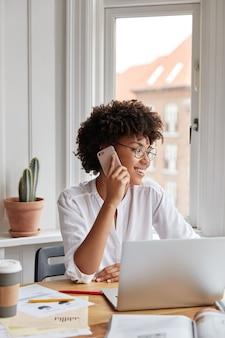 Plan vertical de femme joyeuse comptable parle sur téléphone mobile, a une expression positive, fonctionne avec un ordinateur portable
